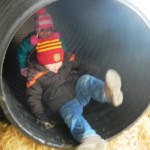 Phillip and Elif glide down the culvert slide at the corn maze.